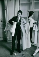 Horst Buchholz on his suit, holding a dress inside the dressing room, 1961.