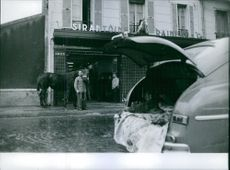 Man standing with horse outside a building, while dicky of the car remain open.