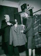 Maurice Auguste Chevalier talking to a lady about his suit.
