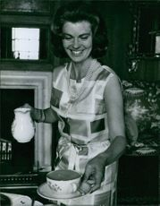Princess Margaretha standing and holding a cup of tea, smiling. 1964