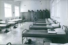 Beds are arranged in a row in a dormitory.