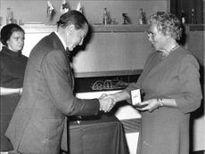 Red Cross chairman Jarl Hjalmarsson awarding a gold medal to Mrs. Ekelund.