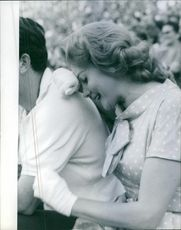 Rhonda Fleming siting with a man and smiling.