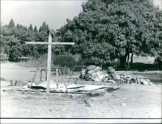 A cross standing in the middle of the field.