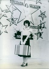 Woman carrying a bag and standing in front of the wall during a scene in film Movie Movie.