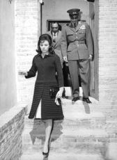 A woman climbing down the stairs with two men following her.