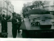 Military men standing with a battle tank on the street.  Taken - 30 Mar. 1962