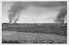 A photograph shows the smoke of a burned area from farm field, 1944.