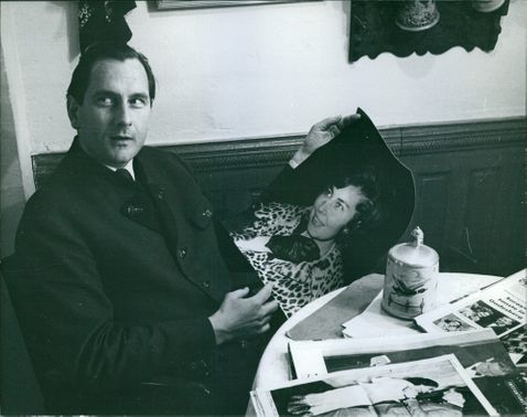 A man sitting on a chair and holding a photograph of a woman.