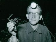 A guy holding a crayfish.