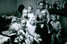 Man sitting with children inside the home.