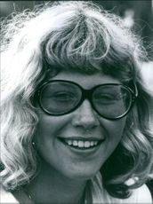 Portrait of a woman wearing eyeglasses and smiling.