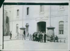 People gathered in front of a building while having conversation during First World War, 1909.