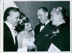 Einar Oscar Beyron talking with other people standing beside him during an event.