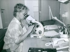 Woman siting in the laboratory and looking through binocular.