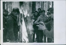 Soldiers standing around the bonfire.