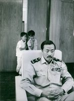 Two boys whispering behind Nguyễn Cao Kỳ.
