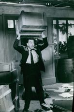 Fernandel standing in a messy room lifting a wooden box looking furious, 1959.