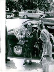 Elsa Maxwell coming out from car with bouquet.