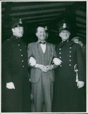 Maurice Auguste Chevalier standing with two another men, folding arms into each other.