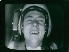 Television displaying a man, laughing and wearing headphone.