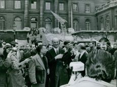 Spectators and press people catch a glimpse of Gaston Naessens (center). 1964.