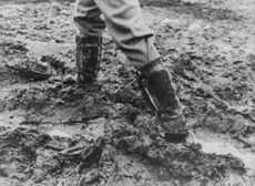 A man standing in mud.