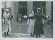 Civilians looking at the traffic enforcer in the street. 1939.