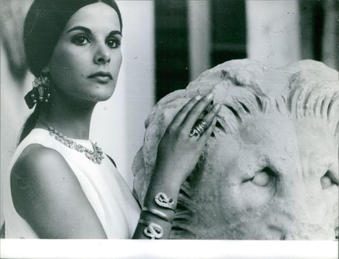 A pretty woman is standing with a Statue of a lion in Greece.