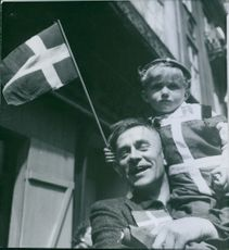 A man carries on his shoulder a child holding a Swedish flag, 1945