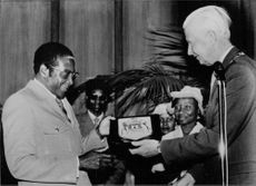 Robert Gabriel Mugabe receiving some gift from a man.