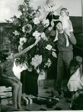 A man and a woman playing with their children.