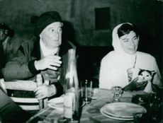 man sitting with Princess Soraya of Iran.