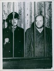 A photo of Vito Mussolini in somewhat resembling the Duce in his appearance, is seen behind iron bars, under guard, as he is taken in the court room for his trials in Milan.
