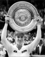 Chris Evert holds up the trophy after winning the final against Hana Mandikova in Wimbledon in 1981