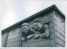 Two soldier looking and smiling from the window of a train.