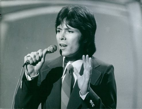 Cliff Richard singing in the stage while standing.