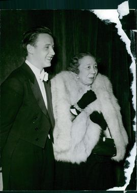A man and a woman standing on ground, smiling.