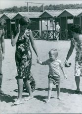 Queen Paola of Belgium walking with her child on sand.