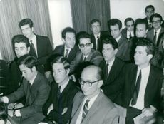 People gathered in a room, sitting and listening.