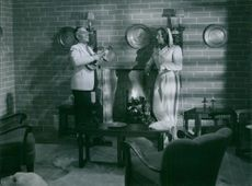 """In the film"""" I natt – eller aldrig"""" Åke Söderblom plays an instrument  while Sickan Carlsson stood by the fireplace and looks at him, 1941."""