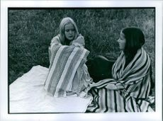 Two women covering themselves with blankets and talking to each other.