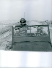 A photo of soldiers riding in a military vehicle.