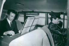 Claude Kahn playing piano inside a vehicle.