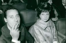 Soraya Esfandiary Bakhtiari sitting with a man in a hall and the man is smoking.