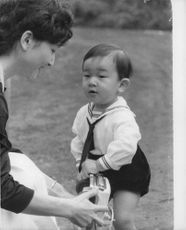 Empress Michiko with her first born so Naruhito playing with a toy car