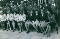 A group of women on a lined up chairs.