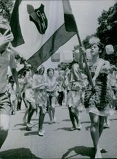 People in procession, woman waving flag. 1964