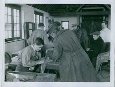 Military troops teaching young teenagers on carpentry.
