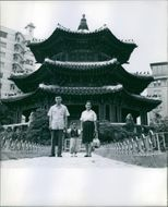 Vintage photo of Kim Ung Yong holding hands with his father and mother in front of a temple. Photo taken on September 22, 1966.